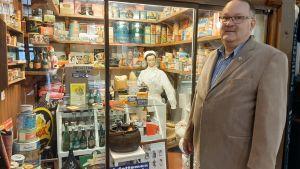 man i glasögon och ljus kavaj står framför museibutik med gamla livsmedelsförpackningar och skyltdocka