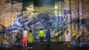 Fem skådespelare står framför ett enormt flygfotografi av ett dagbrott.