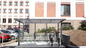 Ett cykelställ under ett tak intill en parkering.