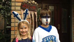 en flicka och en pojke som har FInlands flagga målat i ansiktet