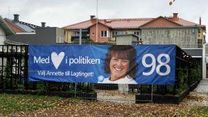 Valbanderoll för Moderaterna på Åland, intill höstlig torgpark i Mariehmn