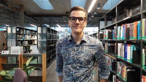 Fredrik Ahlström, glasögonprydd och står framför bokhyllor i ett bibliotek.