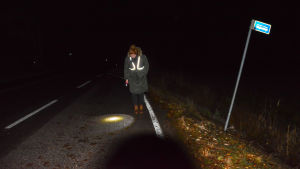 Person i mörker på landsväg.