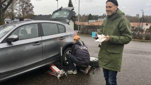 Nicklas Hägen dricker kaffe invid sin bil.