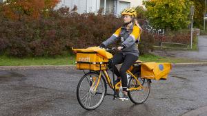 Sara Luostarinen delar ut post på cykel i Böle i Helsingfors.