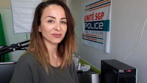 En småleende kvinna i ett kontor med en banderoll med texten Police på väggen.