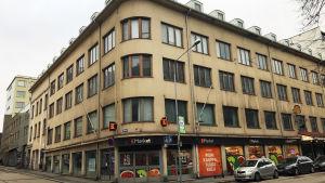 Vaaleanruskea funkis-tyylinen kerrostalo Tuomiokirkonkadun ja Verkatehtaankadun kulmassa edustalla autoja parkissa