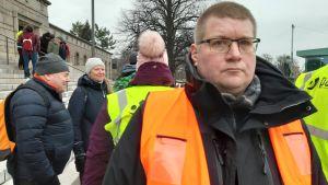 Petteri Syväkari ser bister ut och tittar mot kameran, i orange väst på riksdagshusets trappa, demonstranter i bakgrunden.