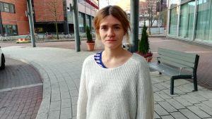 En ung kvinna står utanför ett hotell och tittar in i kameran.
