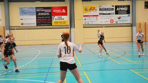 Handbollsspelare på plan. Bollen kastas till en spelare i mitten av bilden, snett mot kameran.