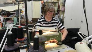 Merja Likitalo syr t-skjortor i företagets syateljé.