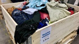 En stor trälåda med avlagda kläder till salu.
