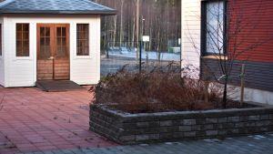 Terrass och gård med stenplattor och lusthus.