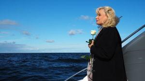 blond kvinna i mörkblå kappa står i båt på öppet hav med en vit ros i sina händer