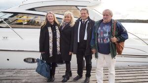 vå kvinnor och två män står framför stor vit båt vid brygga