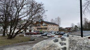 Kontorsbyggnad i trä bakom stenar