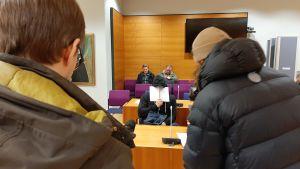 rättegångssal där man håller upp papper för ansiktet.