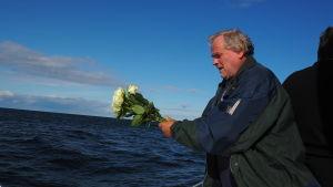 man står på båtdäck på öppet hav med bukett av vita rosor i händerna