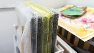 Taiteilijan maalauksia pakattuna kuplamuoviin