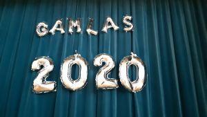 Ballonger på ett draperi där det står Gamlas 2020.