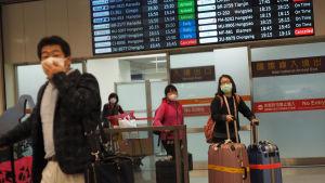 Passagerarna på flygplatsen i Taiwans huvudstad Taipei bar skyddsmasker på söndagen. Samma dag som coronaviruset krävde sitt första dödsoffer i Taiwan, där ett tjugotal människor bekräftats smittade.