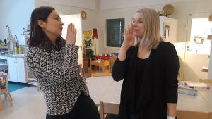 """Angelica Storkamp och Alexandra Östergård visar tecknet för """"ut""""."""