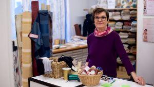 En kvinna står i en tyg- och sytillbehörsaffär.
