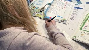 lapsi opiskelee pöydän ääressä kotona