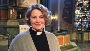 Kyrkoherde Mia Anderssén-Löf framme vid altaret i Nykarleby kyrka.
