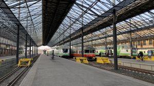 På bilden syns tre stycken tåg som står vid Järnvägstorget. Himlen är blå.