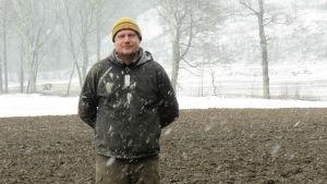 En man med gul mössa och grå jacka står på en åker som delvis är snötäck och delvis är bar. Det snöar ymnigt.