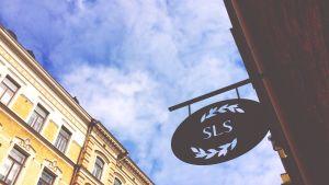 SLS metallskylt på Riddaregatan i Helsingfors fotograferad underifrån mot en blå himmel.