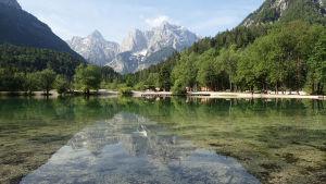 Bergslandskap speglas i vattendrag i Slovenien.