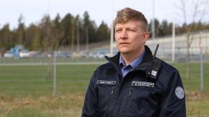 En man i uniform tittar snett till vänster mot kameran.