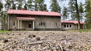 En bild på en grå byggnad i rött tak. I förgrunden syns barr och kottar.
