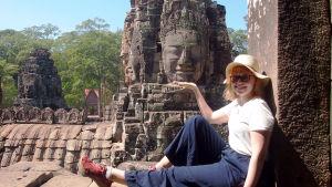 Alina Karvonen ulkomailla istumassa aidan päällä.
