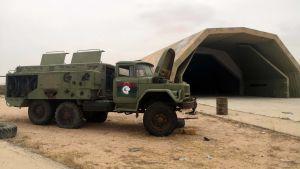 Ett övergivet militärfordon står utanför en hangarbyggnad