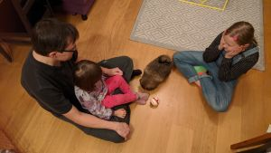En pappa leker med sina barn och sin hund inomhus.