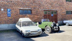 Två veteranfordon, en vit Citroen BX och en grön Alvis parkerade mot en tegelvägg.