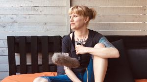 Dokumentaristi Pauliina Motturi istuu sängyllä mikrofonin kanssa.