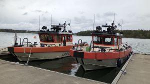två sjöräddningsbåtar ligger vid brygga