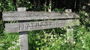 En skylt i grånat träd med texten luontopolku och naturstig.