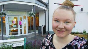 Terhi Numminen står i en blommig blus framför en ingång.