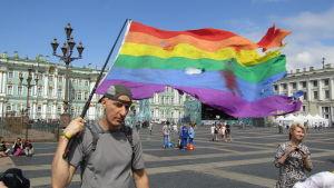 En man går med regnbågsflaggan på ett torg i Ryssland.