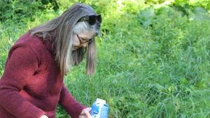kvinna letar efter något på marken