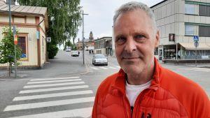 En man i orange jacka tittar rakt in i kameran, där han står på en trottoar i Jakobstads centrum.