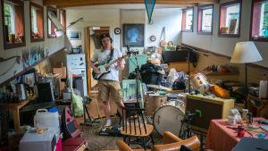 Mies soittaa studiossa.