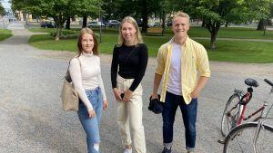 Tre studerande står i en park.