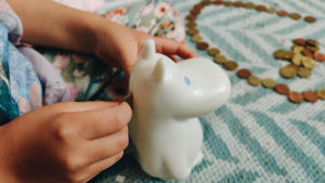 Ett barn lägger in mynt i en Mumin-formad spargris.