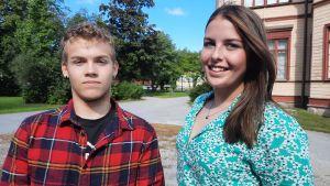 En pojke i rutig skjorta och en tonårsflicka i somrig klänning står på en skolgård.